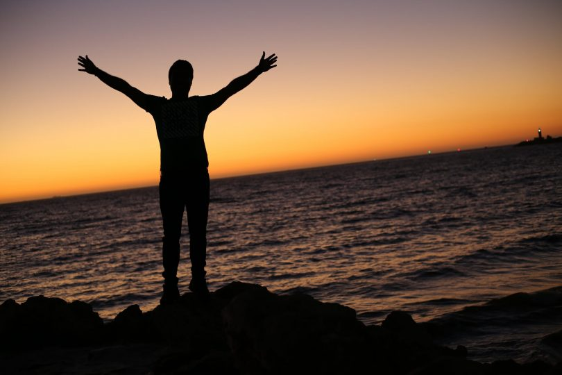 Silhouette of person standing with arms raised in front of ocean.