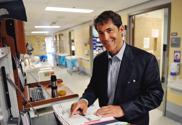 Dr. Geoffrey Cundiff in a hospital hallway smiling at camera.