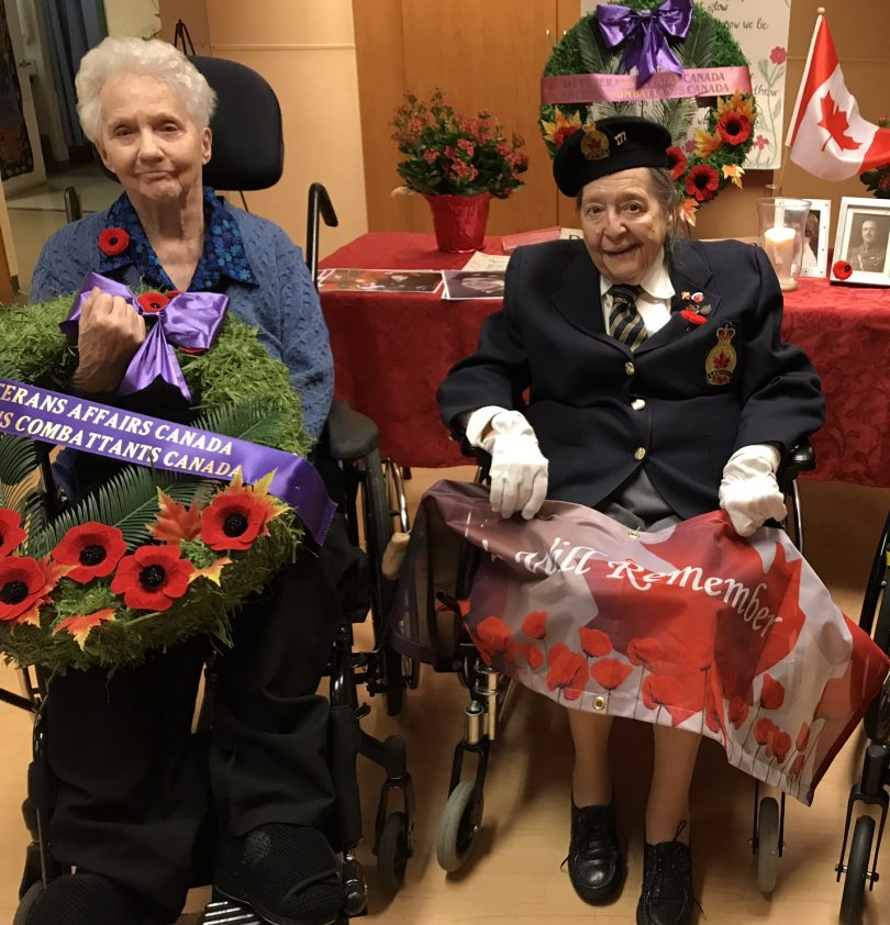 Female veterans at Holy Family (L to R): Penny Sitrling, Colleen de Serres and Geraldine Grimway. The three women are sitting in front of a Remembrance Day display.