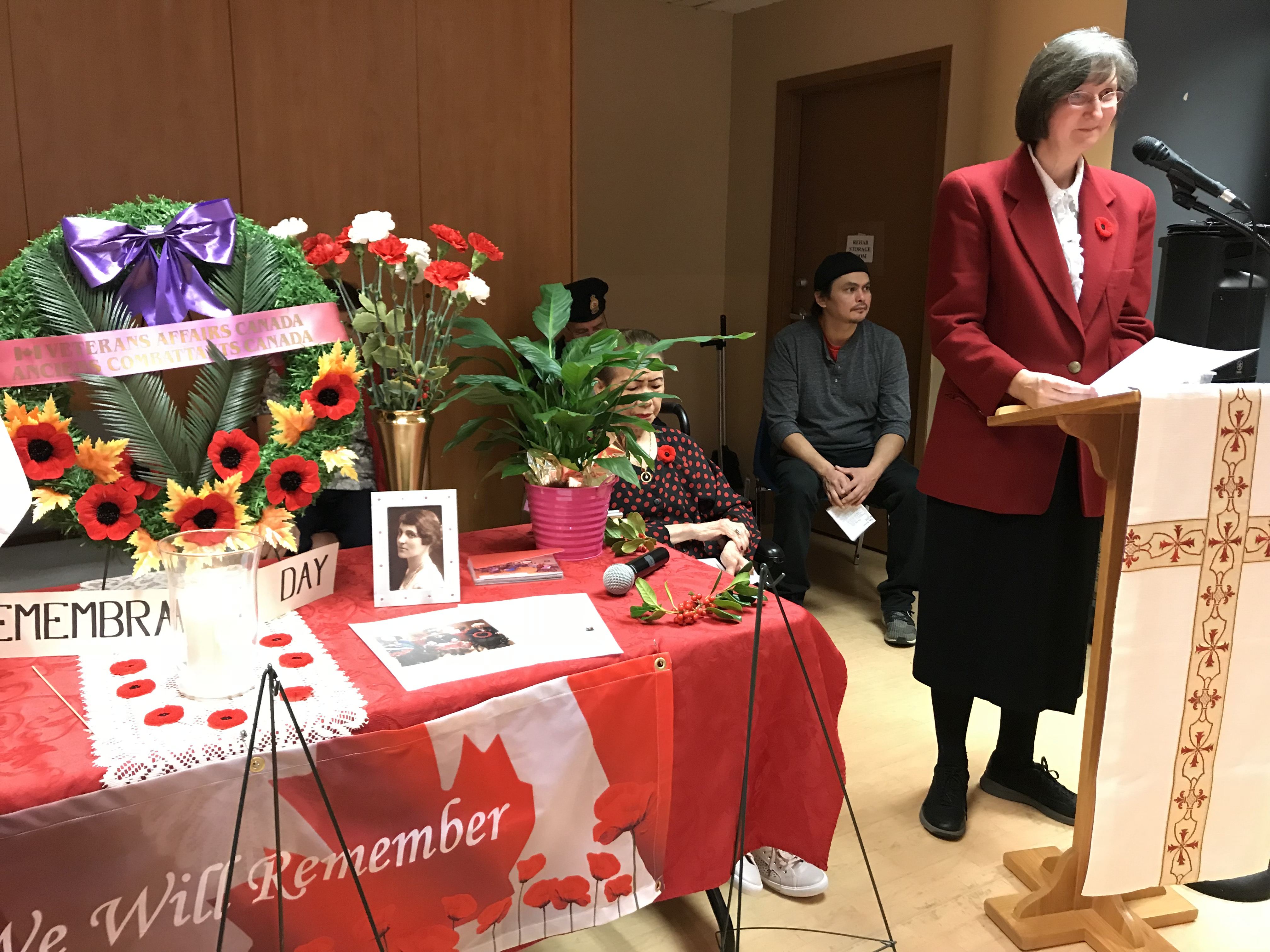 Cecilia Moore at podium with table of Remembrance Day wreaths next to her.
