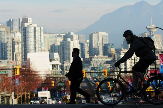 Skyline shot of Vancouver buildings downtown with silhouette of cyclist and biker.