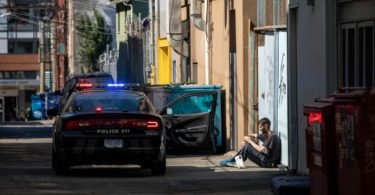 A man has an interaction with police officers in Vancouver's Downtown Eastside on Friday, Sept. 6. (Photo Credit: Ben Nelms/CBC)