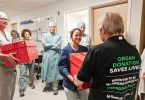 Nurse from OR reaching out to receive box of popcorn from kidney recipient.