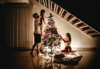Family gathered around a tree with lights, child placing star on tree