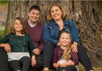Hayley Atkinson, kidney transplant recipient, sitting in front of tree with husband Bill and two daughters.