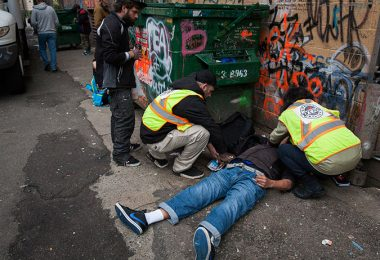 Staff members from the popup safe injection tent prepare the insect a man with Naloxone as he overdoses in a Downtown Eastside alley in Vancouver, British Columbia, November 18, 2016. (Photo Credit: Rafal Gerszak)