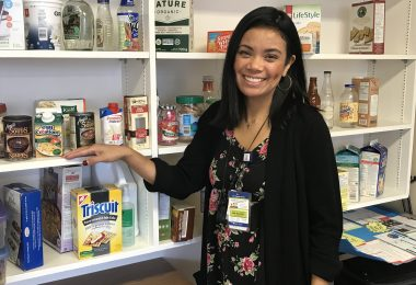 Melodee Dayrit standing in front of shelves with food displays