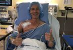 Richard Atkins lying in hospital bed with a smile and two thumbs up.