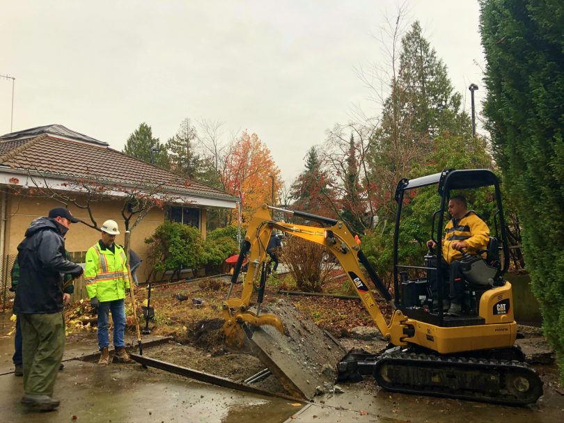 A couple of volunteers from Conwest supervise heavy machinery digging up the ground.