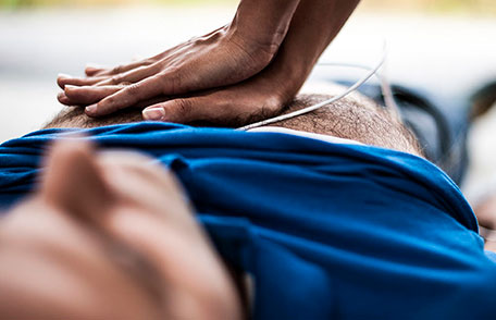 Man lying down with someone's hands doing chest compressions for CPR