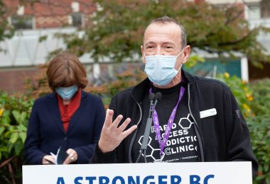 Peer Navigator Mark Haggerty stands at the speaker's podium at a media event on October 12 at St. Paul's Hospital.